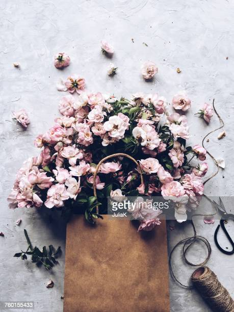 pink flowers in a paper bag - julia rose stock photos and pictures