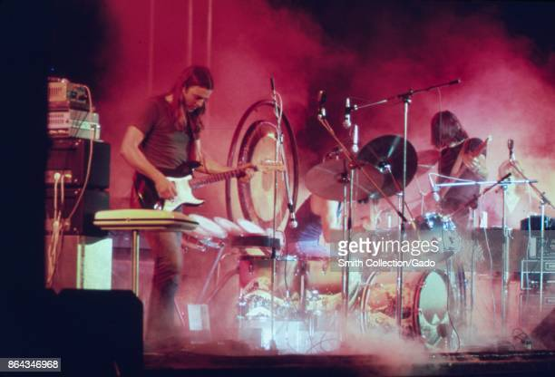 Pink Floyd playing on the stage surrounded with a smoke and illuminated with a red stage lights during the concert at Merriweather Post Pavilion...
