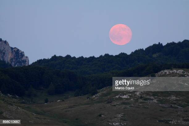 pink full moon over campo imperatore, abruzzo, italy, europe. - pink moon stock pictures, royalty-free photos & images