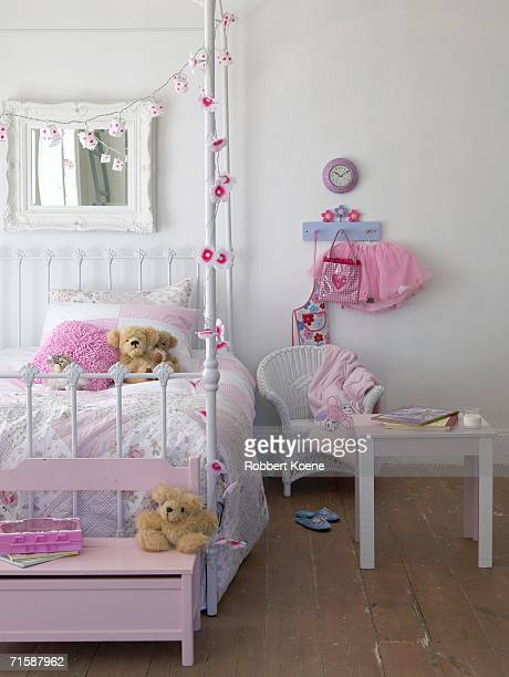 A Pink Girls Bedroom with Side Table and Mirror