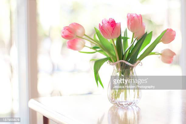Pink glass vase of pink tulips in window