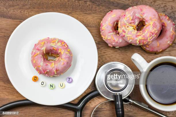 Pink glazed doughnut, donut with sugar sprinkles, stethoscope and cup coffee with DONUT Text. Sweet dessert