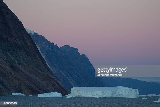 CONTENT] Pink glow of sunrise in Scoresby Sound in North East Greenland The Fjord is fringed by enormous steep mountains that dwarf the huge icebergs...