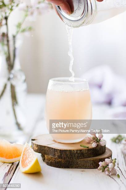 Pink Grapefruit Cocktail Pouring into Glass, with Flowers on White Wood