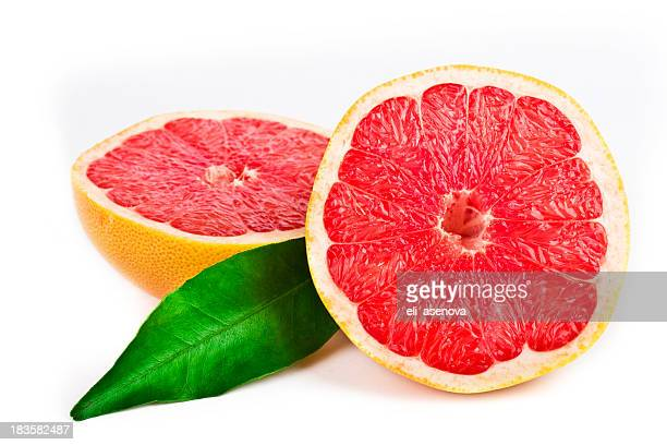 Pink grapefruit cut in half with a green leaf