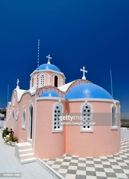 Pink Greek church with blue domes, Karterados, Santorini, Cyclades, Greece