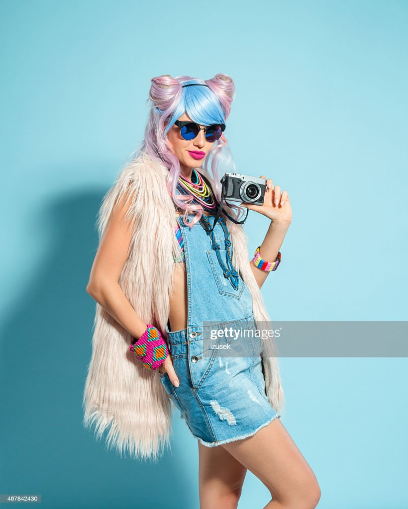 Pink hair girl in funky manga outfit holding camera : Stock Photo