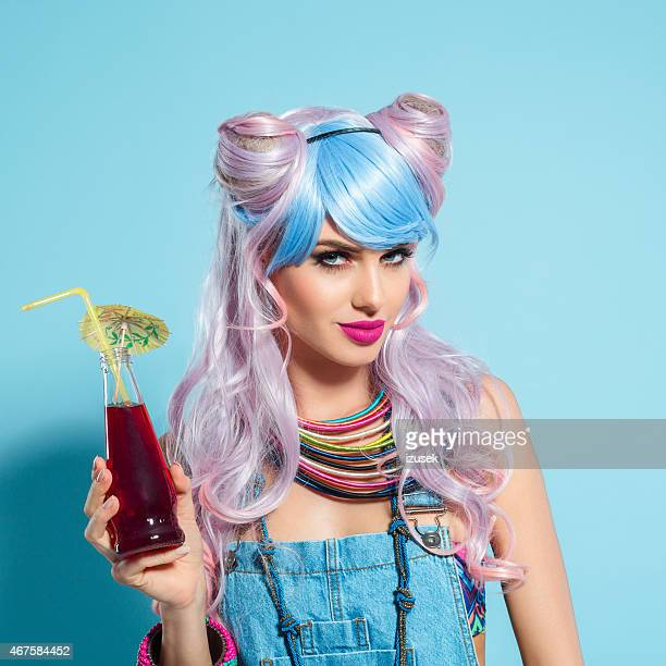 pink hair girl in funky manga outfit holding drink - crazy holiday models stock photos and pictures