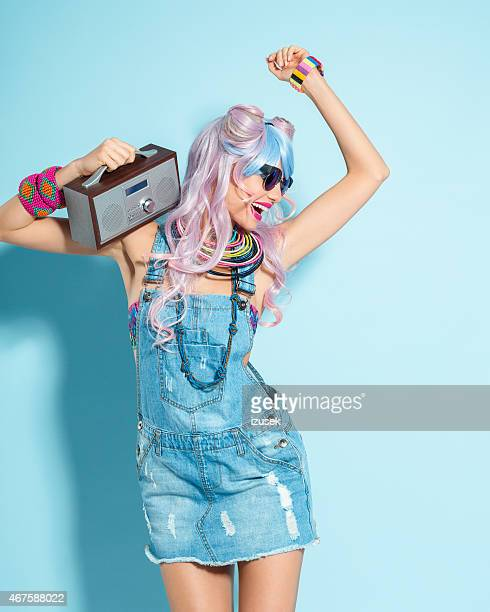 pink hair girl in funky manga outfit holding small radio - crazy holiday models stock photos and pictures