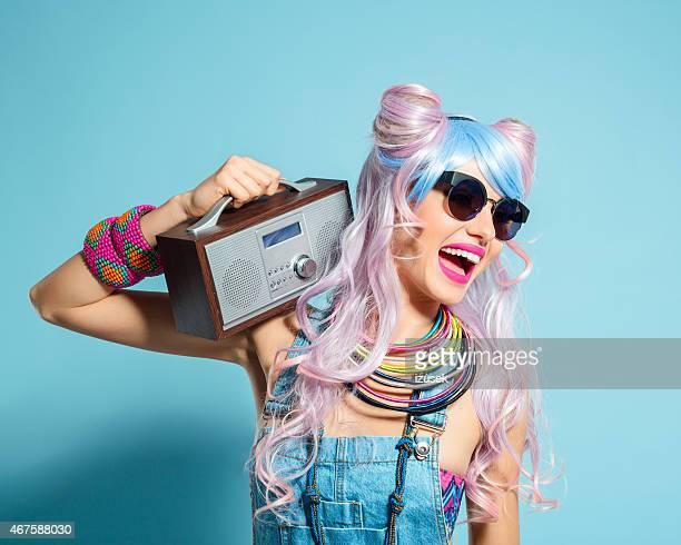 ピンクの髪の女性にファンキーな漫画の装いを持つ小さなラジオ