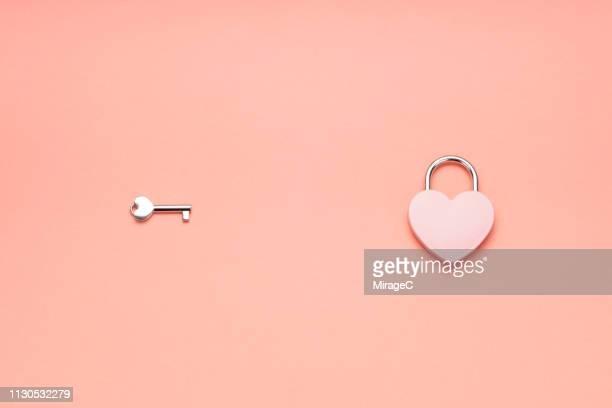 pink heart shape padlock and key - ピーチカラー ストックフォトと画像
