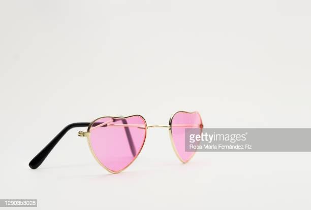 pink heart shaped sunglasses on white background. - offbeat stock pictures, royalty-free photos & images