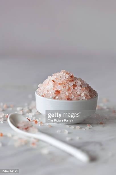 Pink Himalayan salt in the small white bowl and white marble surface