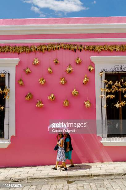 """pink house in calle macedonio alcalá in oaxaca (oaxaca state, mexico) with hanging dried corn on a blue sky - """"gerard puigmal"""" stock pictures, royalty-free photos & images"""