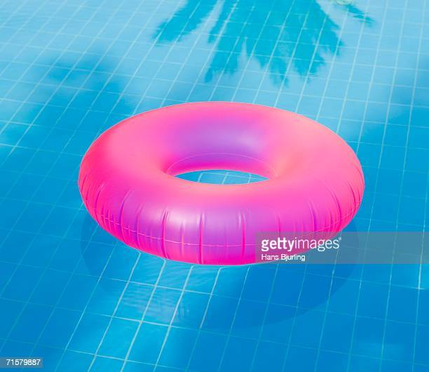 A pink inflatable ring in a pool.