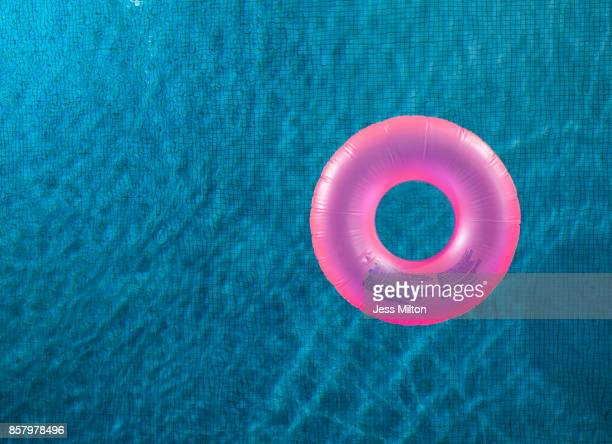 pink inner tube in pool - pink tube photos et images de collection