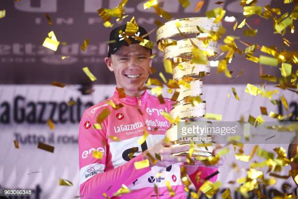 TOPSHOT Pink jersey and winner Britain's rider of team Sky Christopher Froome poses with the trophy on the podium after the 21st and last stage of...