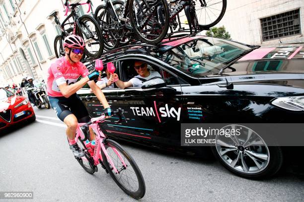 Pink jersey Britain's rider of team Sky Christopher Froome makes a toast with staff members of team Sky during the 21st and last stage of the 101st...