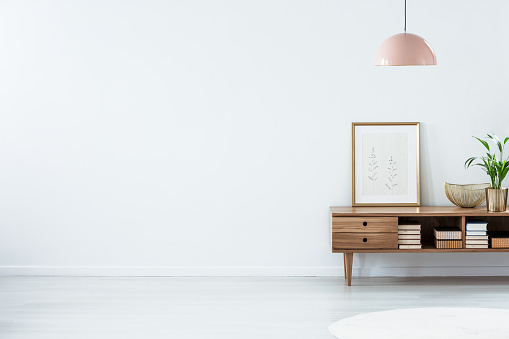 Pink lamp above wooden sideboard 963431642