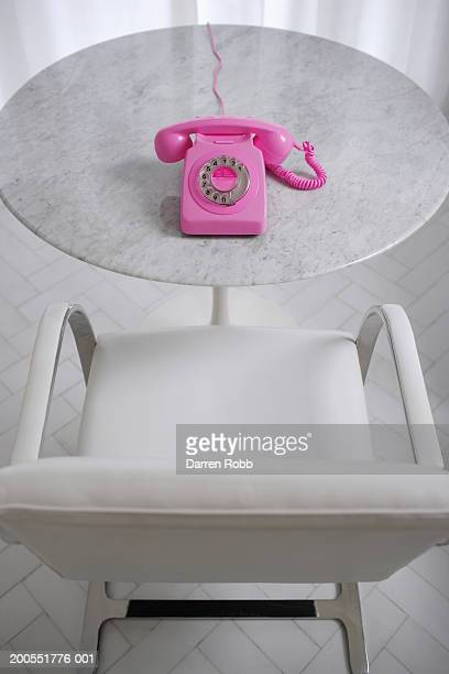 Pink landline phone on table with chair, elevated view
