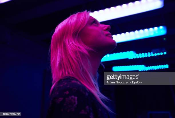 pink light falling on smiling young woman in illuminated room - illuminated stock pictures, royalty-free photos & images