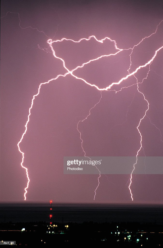 pink lightning bolts crash to the ground below covered by buildings and lights : Stockfoto