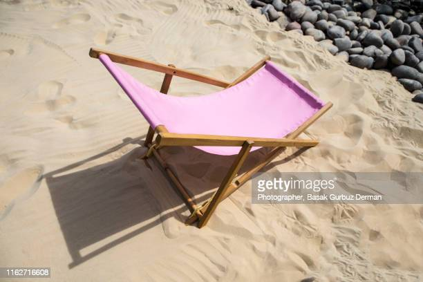 Pink lounge chair on sand in summer