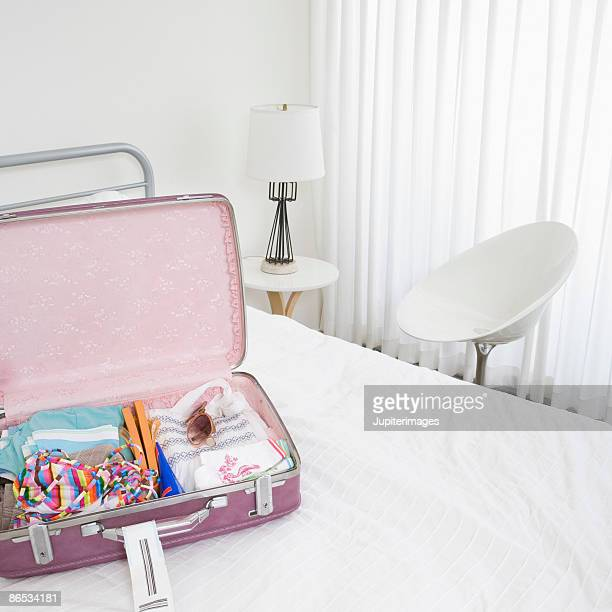 Pink luggage in white room