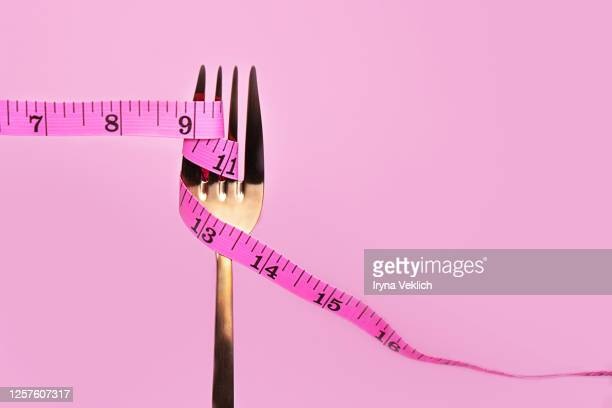 pink measuring tape and fork on pink background. - センチメートル ストックフォトと画像