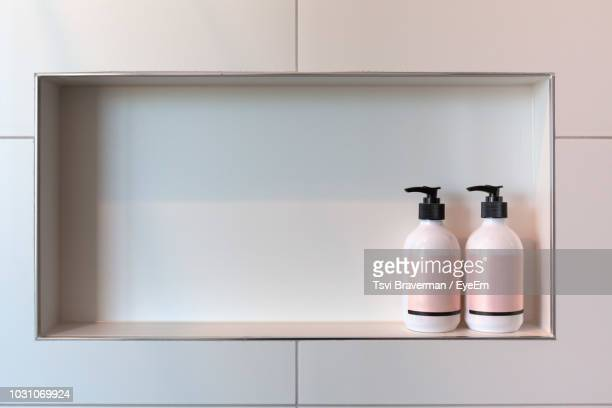 pink moisturizer bottles on wall in bathroom - toiletries stock pictures, royalty-free photos & images