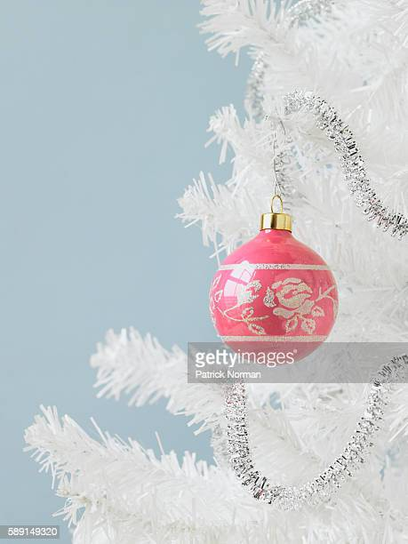 Pink ornament hanging on white Christmas tree