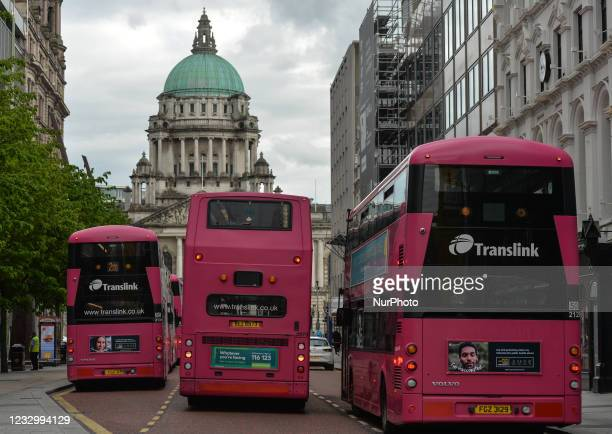 Pink painted buses seen next to Belfast City Hall. On Wednesday, May 19 in Belfast, Northern Ireland