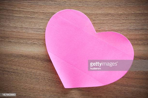 Pink paper heart shape on wood background