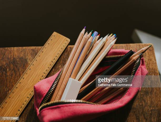 pink pencil case filled with pencils and pens on a wooden table beside a ruler. - pencil case stock pictures, royalty-free photos & images