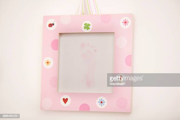 Pink picture frame with footprint of a newborn girl