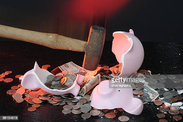 Pink piggy bank being broken by a hammer with coins
