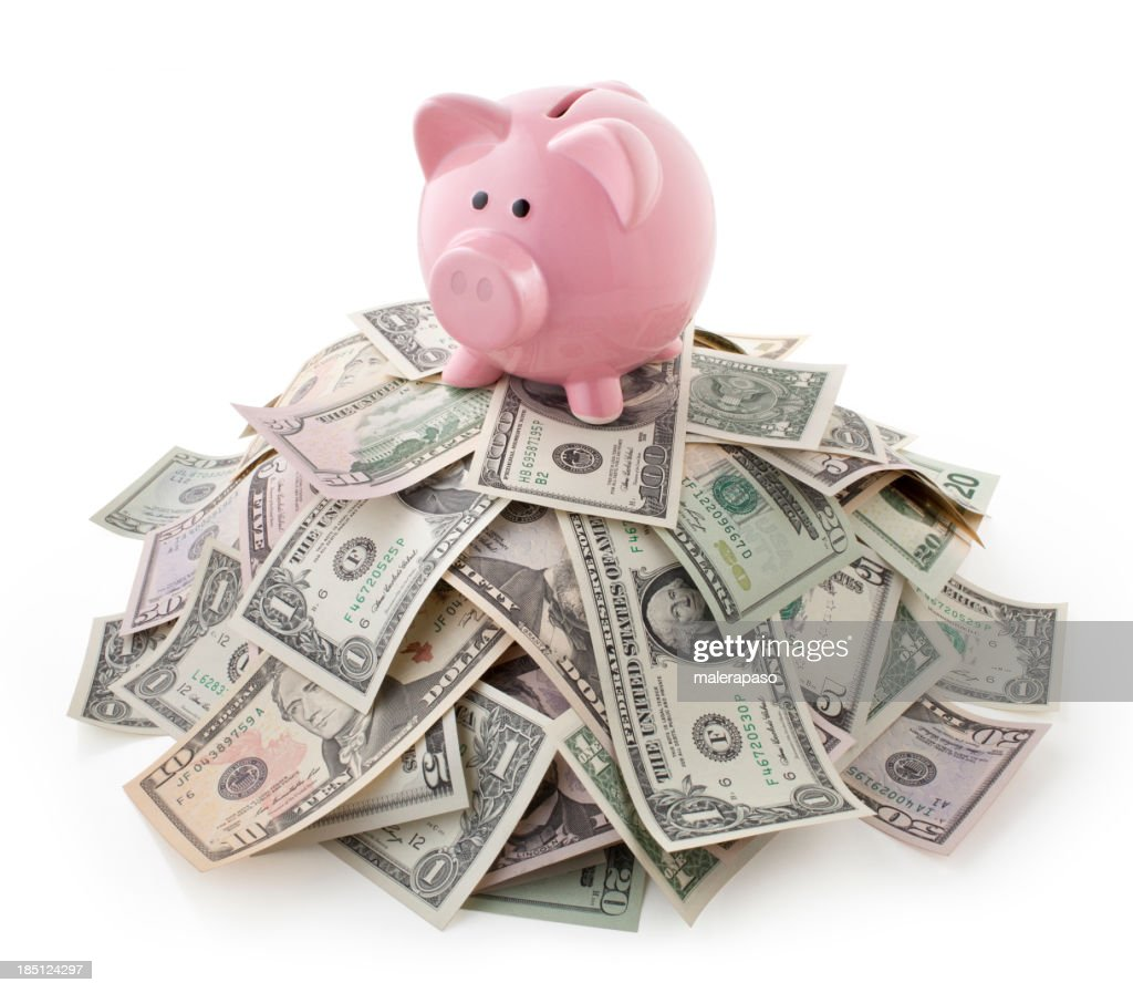 Pink piggy bank on pile of U.S. bills : Stock Photo