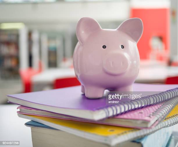 Pink piggy bank on top notebooks - Student loans