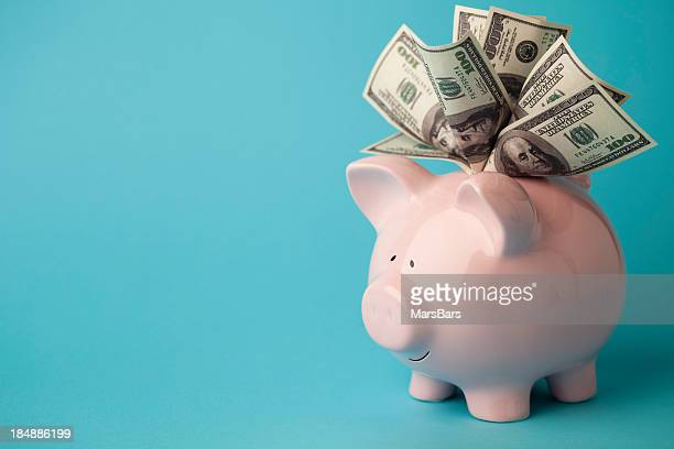 pink piggybank stuffed with dollar bills - american one hundred dollar bill stock pictures, royalty-free photos & images