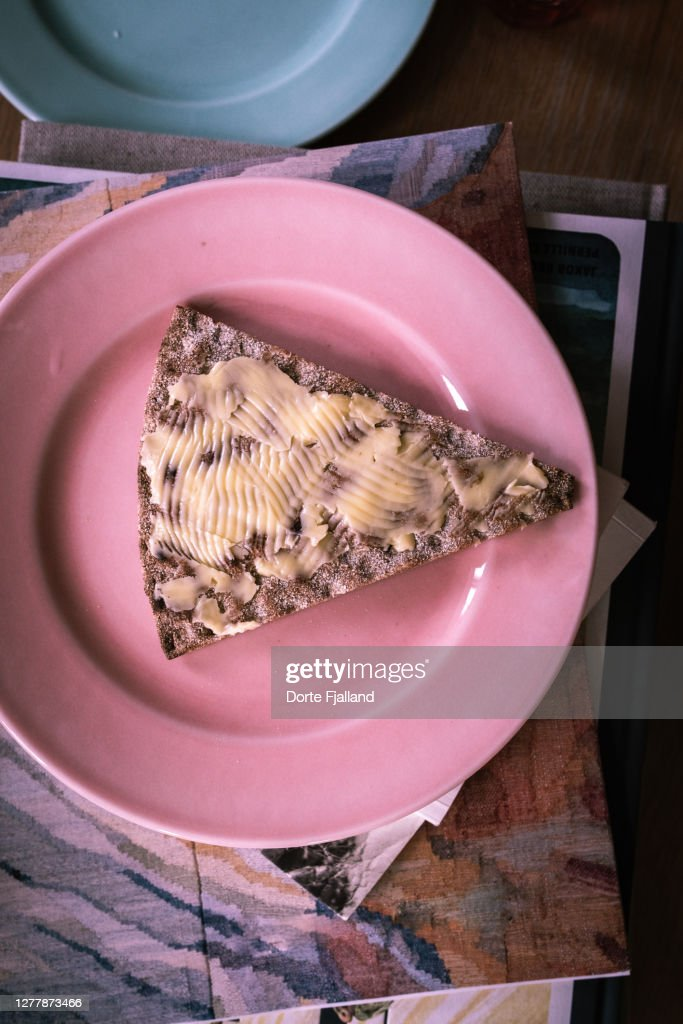 Pink plate with a buttered crisp bread : Foto de stock