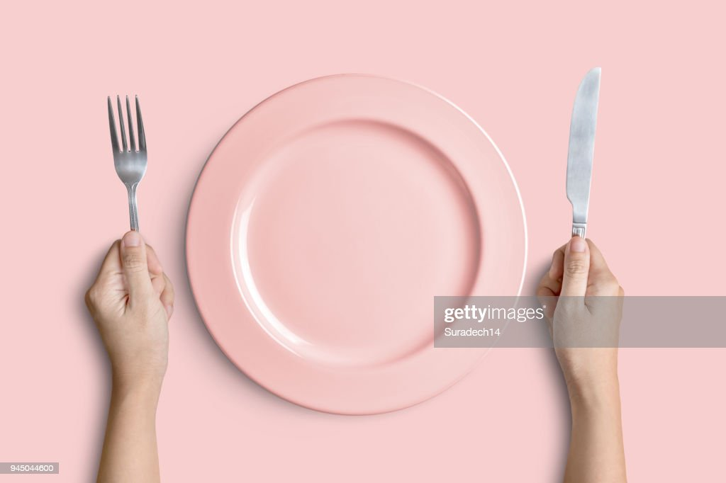 Pink plate with silver fork and knife on pink background : Stock Photo