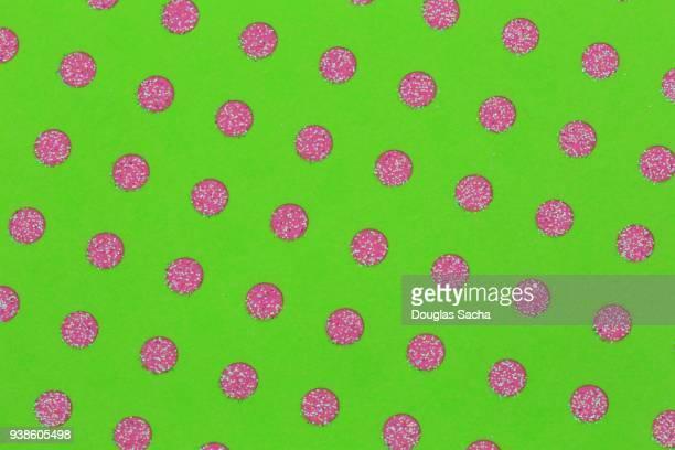 Pink polka dot pattern on green background