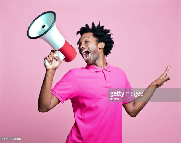 pink portrait of excited young man with megaphone - candidate stock pictures, royalty-free photos & images