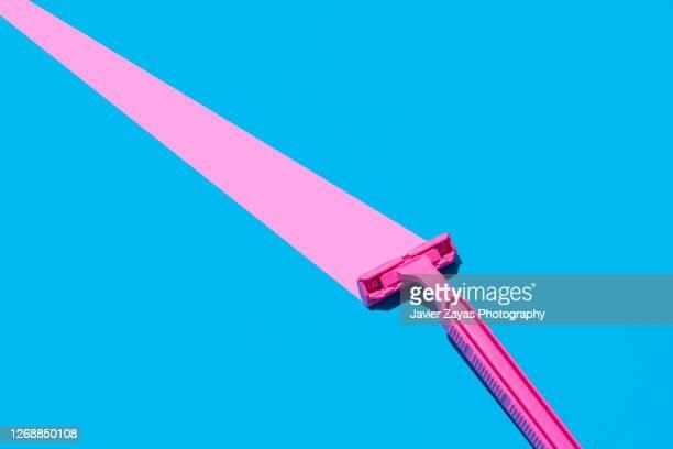 pink razor blade on blue background - potere femminile foto e immagini stock