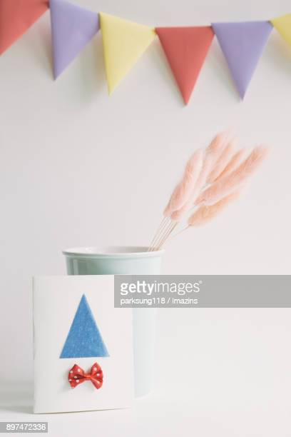Pink reeds in a vase with invitation card