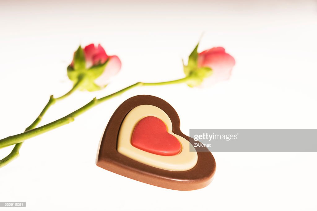 Pink roses and heart shaped chocolate : Stock Photo