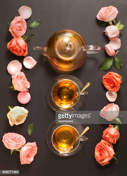 Pink roses and tea set on black table top.