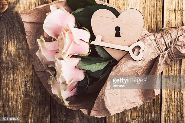 Pink roses and wooden heart and key on a rustic wooden board