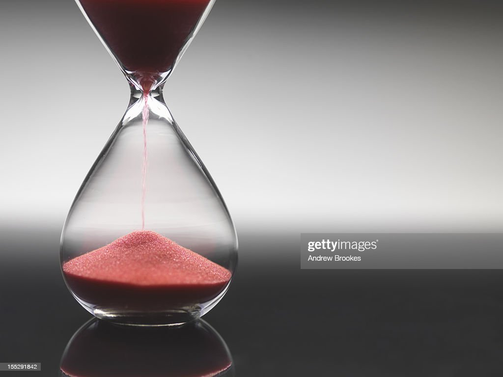 Pink sand pouring through hourglass : Stock Photo