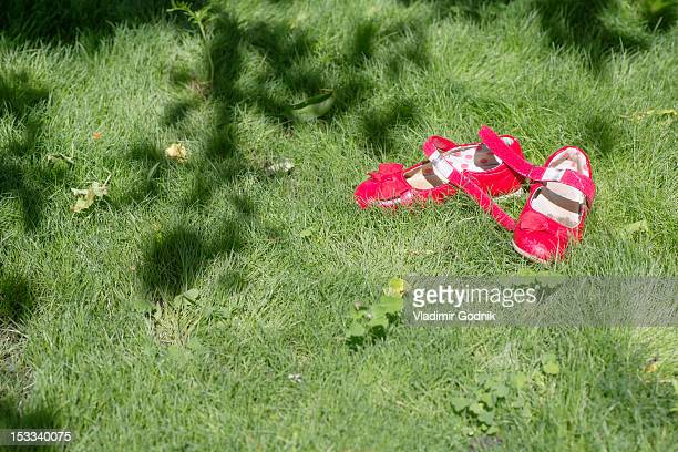pink shoes of a child on grass - nylon fastening tape stock photos and pictures